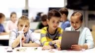 istock kids with tablet pc programming at robotics school 854519692
