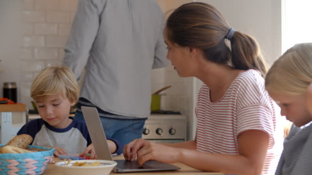 Kids working at kitchen table with mum while dad cooks - Vidéo