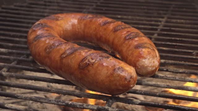 vídeos y material grabado en eventos de stock de salchicha polaca kielbasa cocinar en barbacoa carbón ardiente - dieta paleolítica