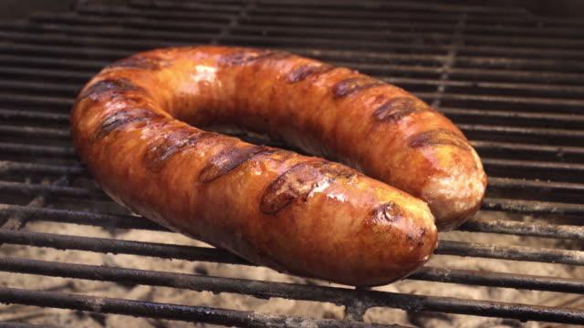 Saucisson polonais kolbassa de cuisson sur un gril Barbecue à charbon ardent - Vidéo