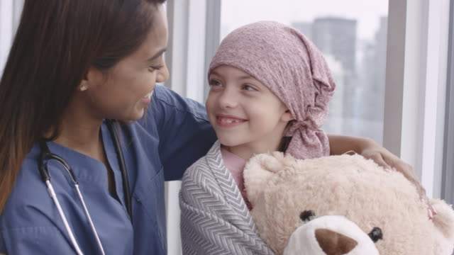 Kind doctor comforts girl with cancer An ethnic doctor sits with child patient. The child is fighting cancer and is wearing a pink scarf on her head. The doctor has her arm wrapped around the girl's shoulder. The girl is holding a large teddy bear. The two individuals are looking at each other and smiling. cancer patient stock videos & royalty-free footage
