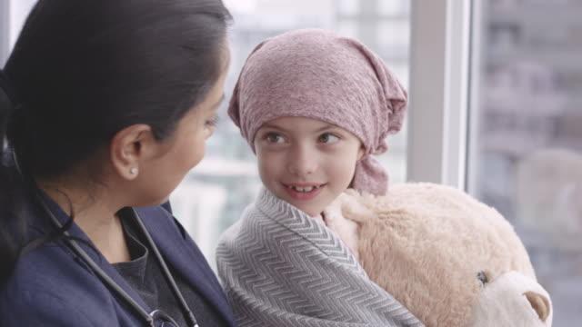 vídeos de stock e filmes b-roll de kind doctor comforts girl with cancer - melhoria