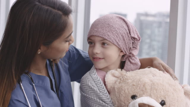 Kind doctor comforts girl with cancer An ethnic doctor sits with child patient. The child is fighting cancer and is wearing a pink scarf on her head. The doctor has her arm wrapped around the girl's shoulder. The girl is holding a large teddy bear. The two individuals are looking at each other and smiling. oncology stock videos & royalty-free footage