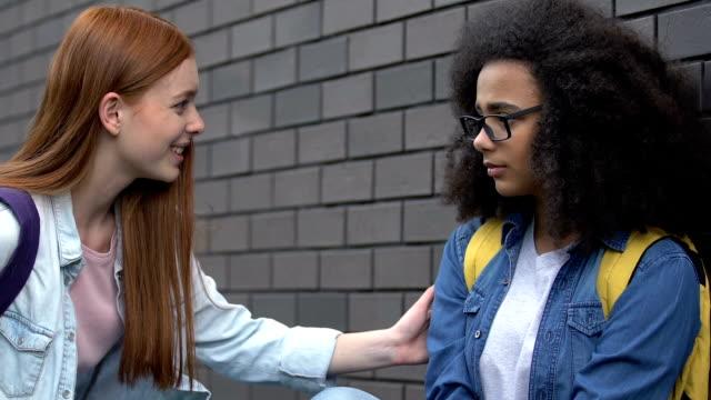 snäll kvinnlig student som ger hjälpande hand till mobbade biracial flicka, sluta rasism - etnicitet bildbanksvideor och videomaterial från bakom kulisserna