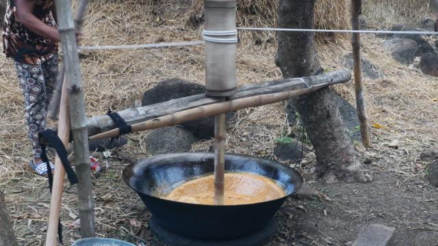 typ av churn trä används för att starta röra palm socker som hjälper det svalna snabbt och börja tjockna - rådig bildbanksvideor och videomaterial från bakom kulisserna