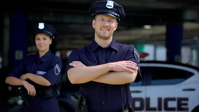 gentili agenti di polizia sorridenti in piedi vicino alla stazione di polizia, pronti ad aiutare, ordinare - polizia video stock e b–roll