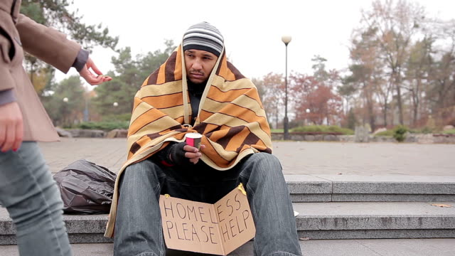 Kind young woman giving money to poor homeless man begging for help in street video