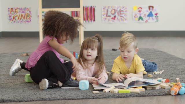 kindergartenfreunde spielen im klassenzimmer - ferienlager stock-videos und b-roll-filmmaterial