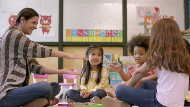 Kindergarten Students in Daycare Young ethnic kindergarten students are playing together in their classroom. They are happily working with their female teacher while being engaged. child care stock videos & royalty-free footage