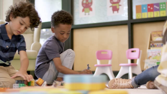 Kindergarten Students Playing Together Two mixed ethnic kindergarten boys are playing together in their classroom. They are happily working with with one another. child care stock videos & royalty-free footage