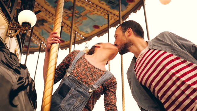 Kiss on a carousel ride Video of a young, romantic couple who enjoy the carousel ride in front of an Eiffel tower in Paris, France, kissing each other. kissing stock videos & royalty-free footage