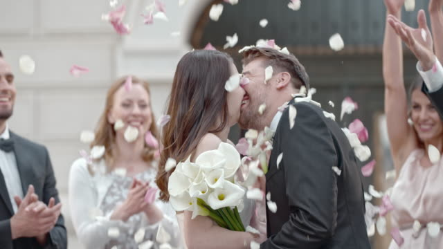 slo mo kissing newlyweds being showered with rose petals - bouquet video stock e b–roll