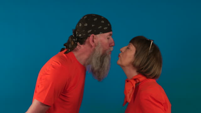 Kissy Kissy Senior couple standing in front of a blue studio background leaning forwards to kiss each other. face to face stock videos & royalty-free footage