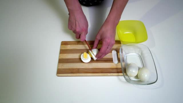 vidéos et rushes de cuisine. gros plan. une jeune femme se prépare la nourriture. mains du close-up de fille. une femme coupe œufs à la coque pour faire une salade. - recette