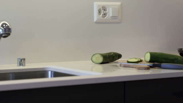 Kitchen countertop made of the granite slab. Kitchen cabinets are made of black flat panels.