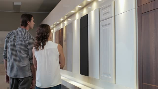 Kitchen decorating browsing shopping Couple browsing samples  of cabinets cupboards in modern kitchen showroom home remodeling, renovation and makeover concept cabinet stock videos & royalty-free footage