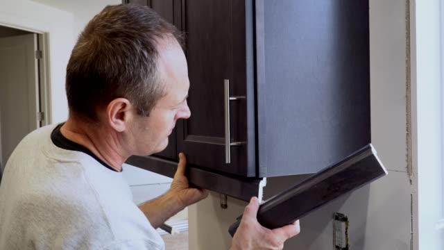 kök installation man händer installation kök i gjutning för köksskåp - looking inside inside cabinet bildbanksvideor och videomaterial från bakom kulisserna