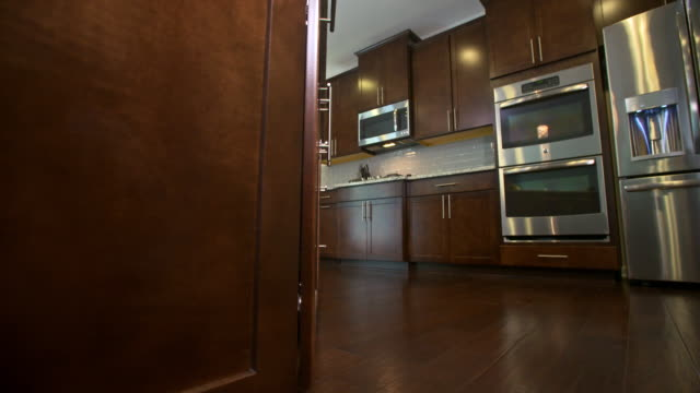 Kitchen Low Angle Reveal Appliances and Cabinets camera slowly moves right to reveal kitchen from the island. Dark brown wood cabinet stock videos & royalty-free footage