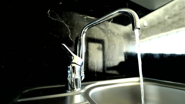 Kitchen Sink on Granite Counter - 4K Resolution Turning On a Faucet and Off, Kitchen Tap, Kitchen Sink, Kitchen, Stainless Steel, Granite, 4K Resolution kitchen sink stock videos & royalty-free footage