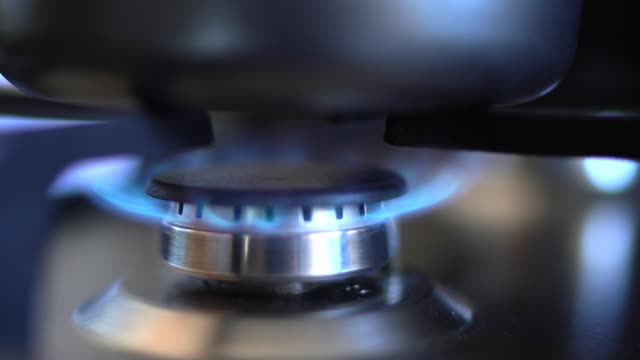 vídeos de stock e filmes b-roll de kitchen stove with blue flames burning (turning on) - gases