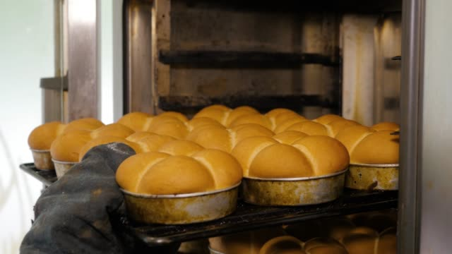 Kitchen worker takes out the buns from the oven in bakery. Kitchen worker takes out the buns from the oven in bakery. bun bread stock videos & royalty-free footage