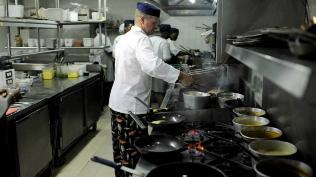 Kitchen Workers Food being prepared in a commercial kitchen. commercial kitchen stock videos & royalty-free footage