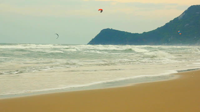 Kiteboarder ride over the waves in the sea