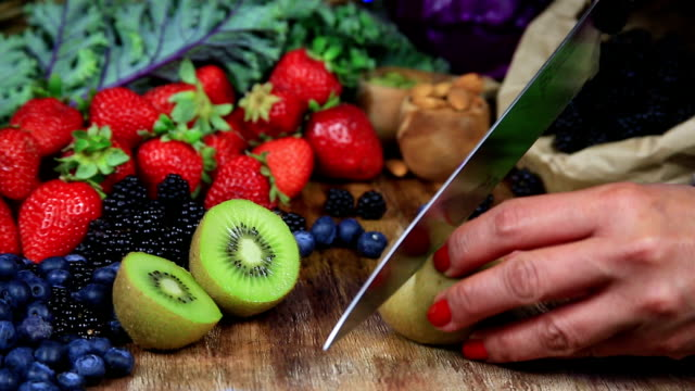 Kiwi Cutting Cutting Kiwi on a Table Filled with Fresh Fruits nutritionist stock videos & royalty-free footage