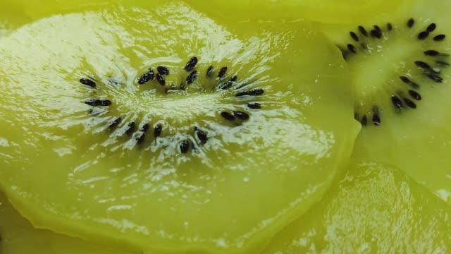 kiwi-früchte schneiden rotierend. ansicht von oben. mit lärm und burry bokeh hintergrund. - indochina stock-videos und b-roll-filmmaterial