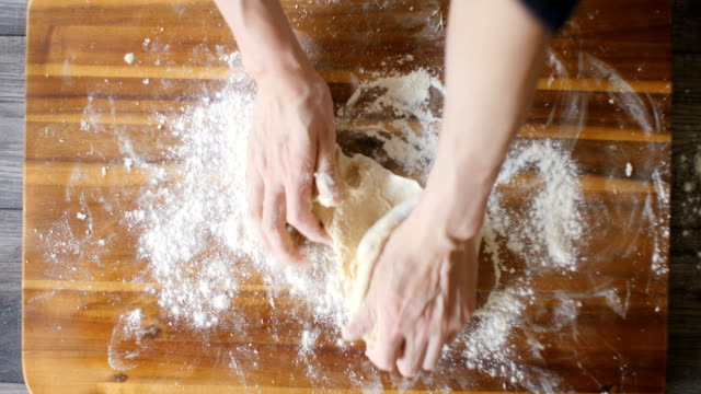 kneading bread dough for making english muffins - impasto video stock e b–roll