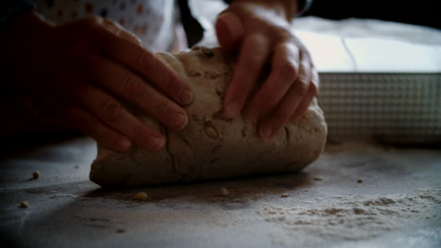vídeos de stock e filmes b-roll de kneading loaf of bread with hands - assado no forno