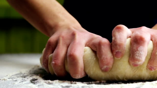 kneading the dough by hand Baker kneads the dough by hand on the table dough stock videos & royalty-free footage