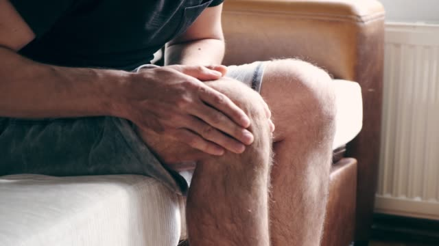 Knee pain Man having terrible knee pain, and trying to massage on it. ankle stock videos & royalty-free footage