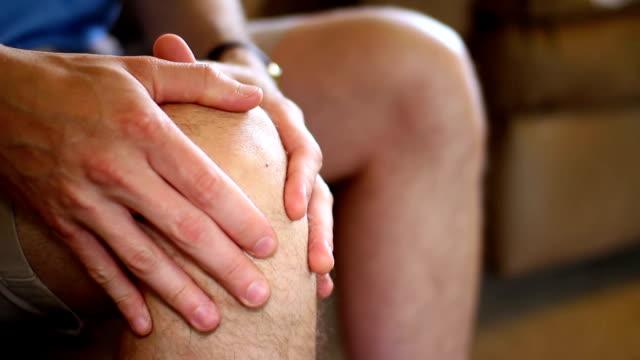 Knee Pain A man rubs his aching knee. knee stock videos & royalty-free footage