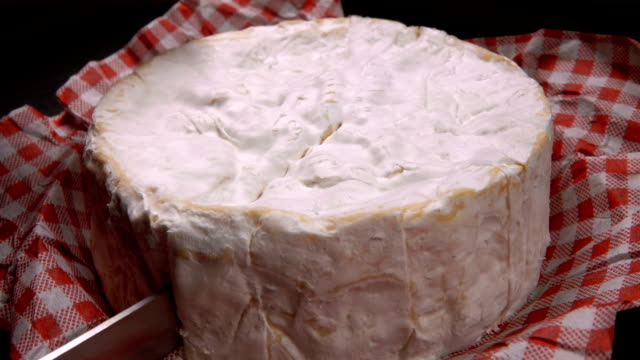 knife carves a sector of round camembert cheese - french food stock videos and b-roll footage
