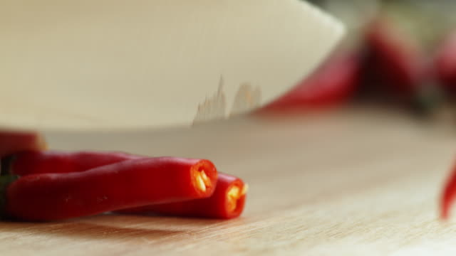 knife chopping red chili pepper for cooking spicy thai food - slow motion - peperoncino video stock e b–roll