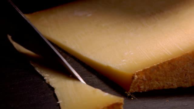 vidéos et rushes de couteau coupe un fromage dur en tranches sur une surface noire - parmesan