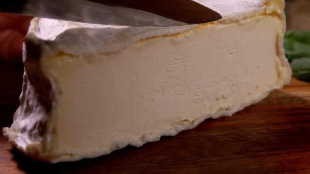 messer schneidet ein stück weiche ziege köstlichen käse - brie stock-videos und b-roll-filmmaterial