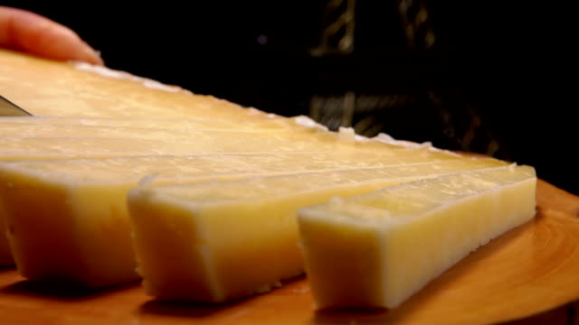 Knife cuts strips of hard cheese - video
