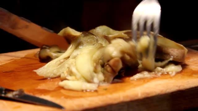 coltello taglio di un bollito melanzana su un taglio tavolo - melanzane video stock e b–roll