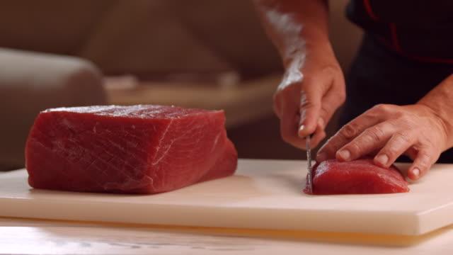 Knife cutting meat on board. video
