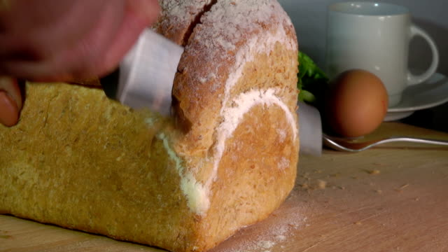 Knife cutting off a loaf grain bread Slow motion of knife cutting off a loaf grain bread cooking utensil stock videos & royalty-free footage