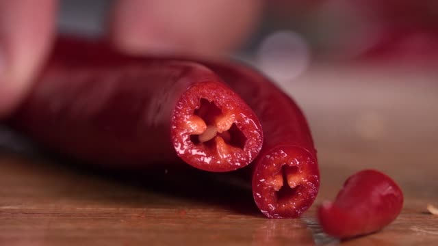 knife cutting red chilli pepper on wood - peperoncino video stock e b–roll