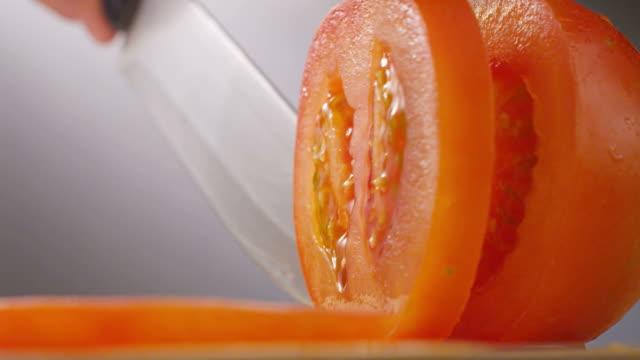 vidéos et rushes de couteau couper tomate - aliment en portion