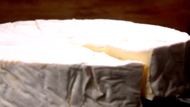 messer hebt einen sektor der runde brie-käse - brie stock-videos und b-roll-filmmaterial