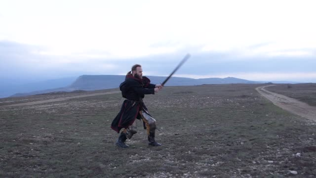 Knight fencing his sword against the backdrop of the mountains at sunset Knight fencing his sword against the backdrop of the mountains at sunset Slow motion video knight person stock videos & royalty-free footage
