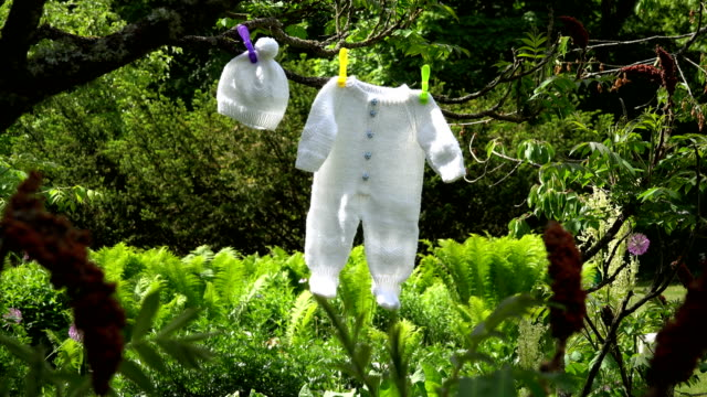 knitted white baby bodysuit and hat hang on tree branch in garden. - copricapo abbigliamento video stock e b–roll