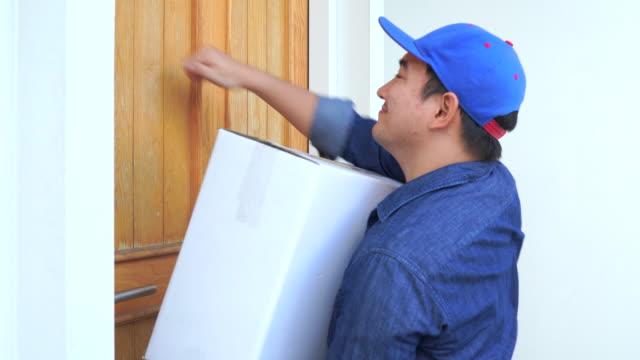 vídeos de stock e filmes b-roll de knock delivery man in blue uniform hand parcel box to recipient - door knock