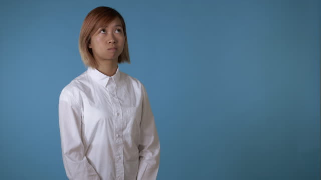 korean girl thinking about something important close up face young asian businesswoman posing finding best idea on blue background in studio. attractive korean woman with blond hair wearing white casual shirt looking at the camera genius stock videos & royalty-free footage