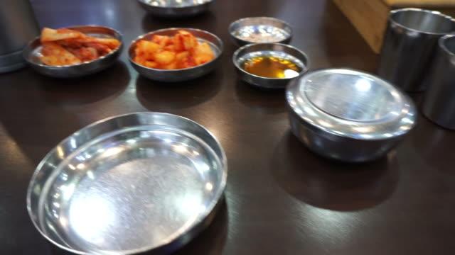 vídeos de stock, filmes e b-roll de restaurante coreano configurar com utensílios de aço inoxidável como cultura popular tradicional, para cozinha - comida salgada